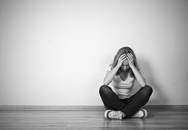 girl sits in depression on floor near the wall
