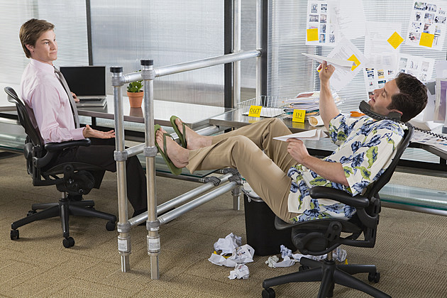 Playful businessman aiming paper airplane at serious co-worker