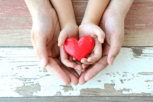 Red heart in child and mother's hands